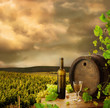Wine, barrel and vine on background of early evening vineyard