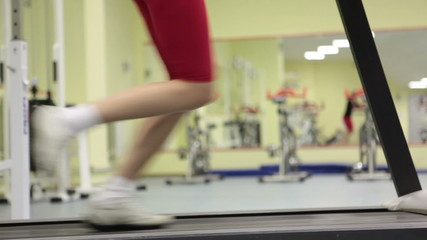 Young woman doing exercise against mirror in sport club