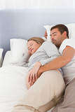 Lovely future parents sleeping in the bedroom