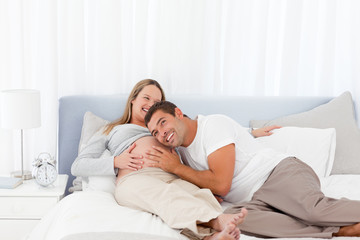 Funny man putting his head on the belly of his pregnant wife