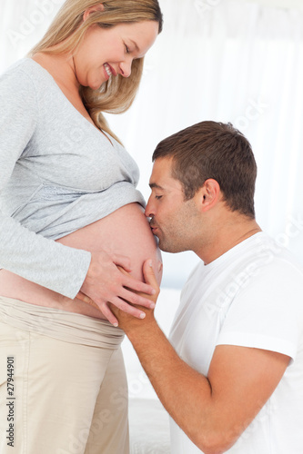 Adorable future dad kissing the belly of his wife