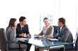 Businessmen and businesswomen talking during a meeting - 27945156