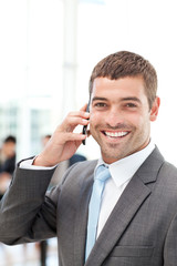 Happy hispanic businessman on the phone while his team is workin