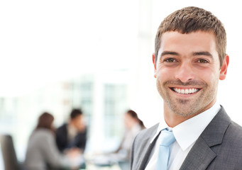 Businessman smiling at the camera while his team is working