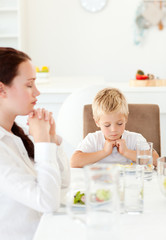 Concentrated little boy praying with his mother before eating th