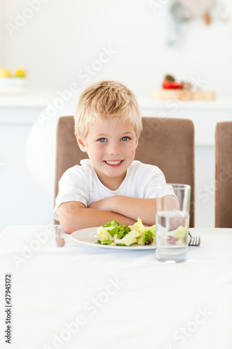 Cute little boy ready to eat his salad for lunch sitting at a ta