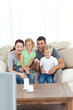 Happy family laughing while watching television sitting on the s