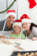 Cheerful family kneading biscuits for Christmas