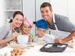 Portrait of a joyful family cooking littles cakes