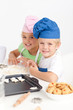Adorable siblings kneading together a dough in the kitche