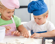 Young brother and sister kneading a dough to make cakes