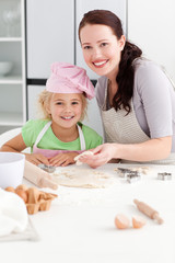 Portrait of a happy mother and daughter kneading a dough