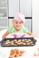 Adorable little girl shoing her cookies to the camera