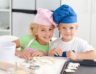 Portrait of two adorable children baking in the kitchen