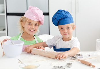 Happy brother and sister preparing a dough standing in the kitch