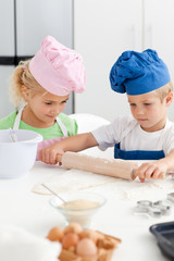 Little girl looking at her serious brother using a rolling pin