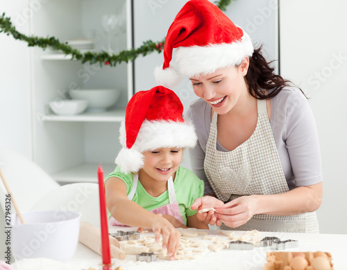 Lovely mother and daughter preparing Christmas cookies