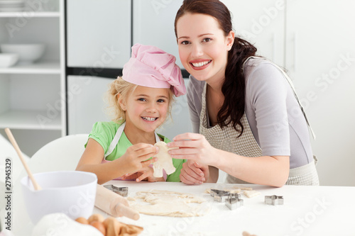 Cute daughter and mother showing a cookie in form of a man
