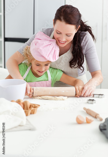 Beautiful mother and her cute daughter using a rolling pin