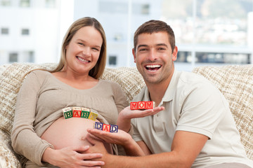 Cheerful couple holding letters sitting on the sofa