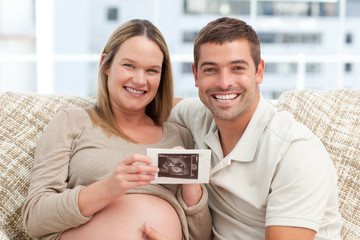 Joyful future parents looking at an echography together