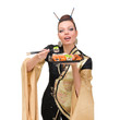 Woman wearing a traditional dress eating sushi, isolated