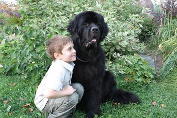 Мальчик в обнимку с черным ньюфаундлендом на фоне зелени