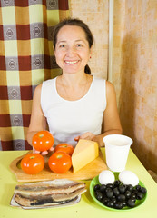 Cook with ingredients for stuffed tomato. Cooking in series