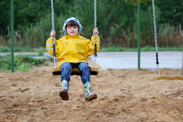 Adorable toddler girl in yellow rain coat on swing