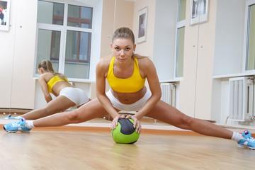 Sports blonde girl do the splits in gym