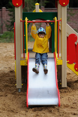 young girl in yellow rain coat playing on a slide in a park