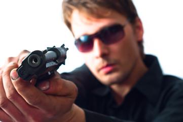 Man holding gun in dirty hands with focus on pistol  weraing sun