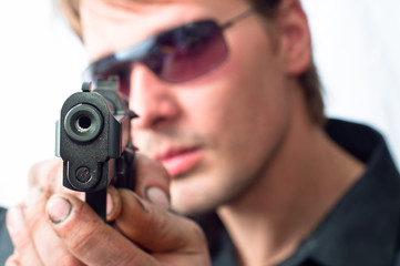 Man aiming with pistol wearing sunglasses