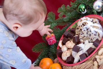 Baby greift nach Weihnachtsteller
