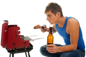 smoking young man grilling chiken and drinking beer