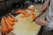 A cook cut carrots in the kitchen of a restaurant