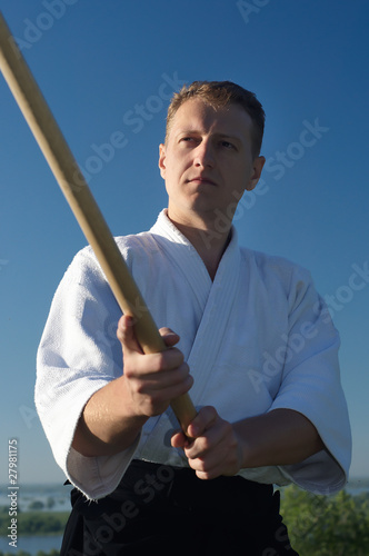 Young master Ajkido with a bokken in hands on the blue sky