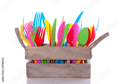 colorful plastic cutlery in a wooden crate isolated over white