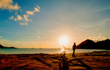 Sunset beach with a silhouette of boy and bicycle