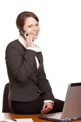 Junge attraktive Frau telefoniert  im Büro mit Handy