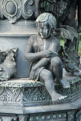 Statue of young boy sitting on a fountain