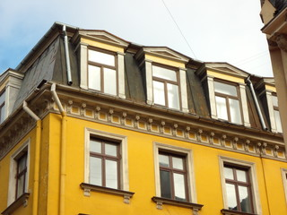 Yellow building with mansard and glittering windows