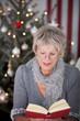 ältere dame liest vor dem weihnachtsbaum