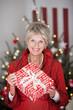 lächelnde seniorin mit weihnachtsgeschenk