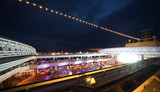 People enjoy night party on the deck of illuminated cruise ship