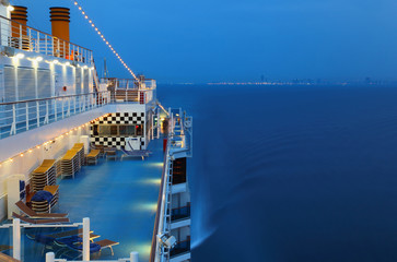 Illuminated cruise ship with people in sea at night near city