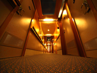 Narrow and illuminated corridor with hotel rooms in cruise ship