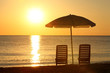 Two empty chairs stand on  beach under  opened umbrella with  vi