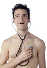 jeune homme souriant écoutant son coeur au stétoscope