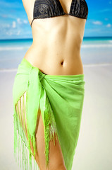 Fine female body in bikini on beach
